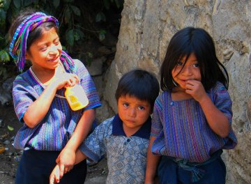 Three Guatemalan children in the colorfully-woven clothing of the native peoples shyly smile at the camera.