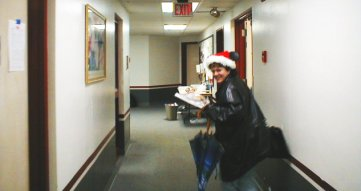 Dr. Jessica Kun in a Santa hat running away from the camera