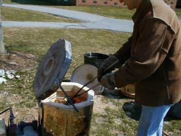 Milt Friedly pulls pottery from kiln with tongs.