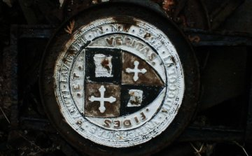 An iron-cast university seal at Sahd's metal salvage and recycling